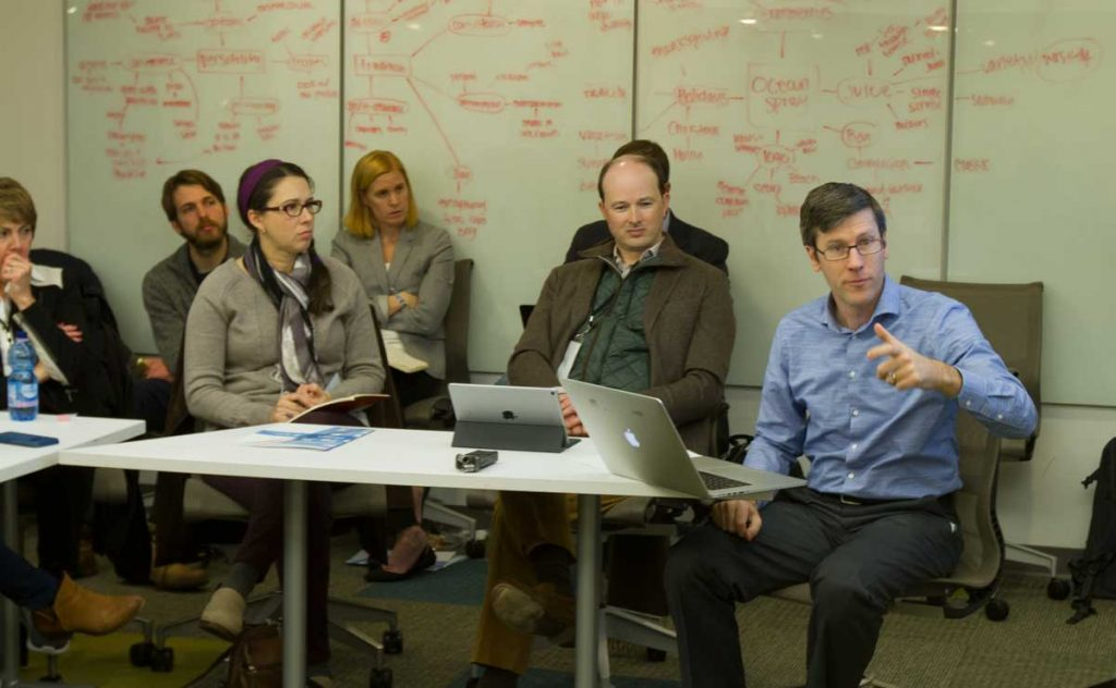 Photo of Ryan Thornburg (far right) speaks to a group of media leaders during their Innovation Mission visit to the UNC School of Media and Journalism.